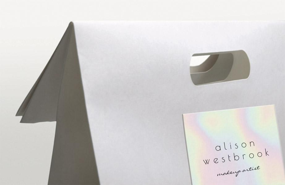 Pochette cadeau kraft blanchi avec rabat simple et poignées découpées, embossage et marquage à chaud holographique et noir